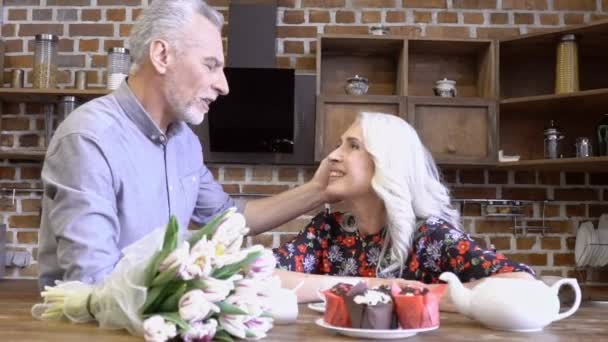 Happy lovely elderly couple sitting and talking together on kitchen at home