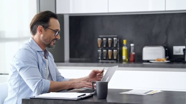 Side view of smiling mature man in shirt and eyeglasses sitting by the table while using laptop computer with credit card in hand at home