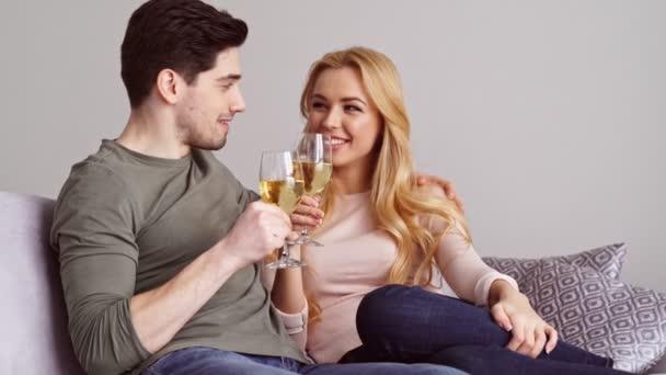 glückliches junges Liebespaar sitzt zu Hause auf dem Sofa und trinkt Alkohol Weißwein Champagner
