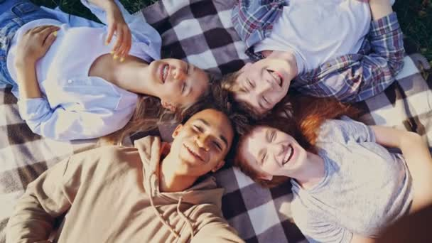 Mutlu çok ırklı öğrenciler grubu birlikte eğleniyor ve parkta dışarıda yatarken selfie çekiyor