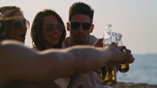 Close up view of young smiling friends drinking beer and having fun time together at beach near the sea