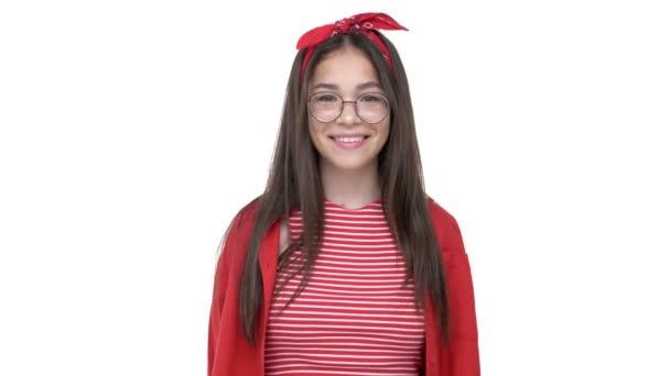 Krásná mladá dívka v červeném tričku se usmívala a dívala se na kameru přes bílý pozadí