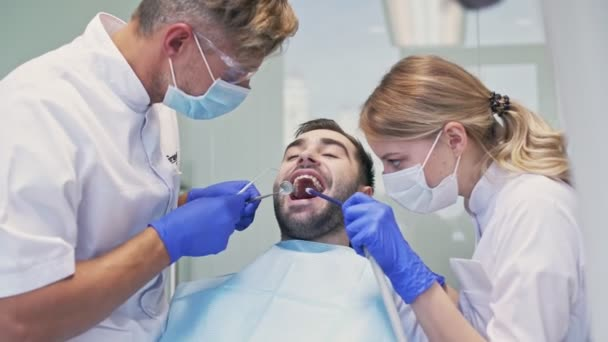 Handsome brunette man smiling while having dental procedure with dentist and assistant at the dental clinic