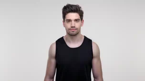 Súlyos fiatal szakállas sportos férfi fekete inget mondván, és nem rázta a fejét, miközben nézte a kamerát szürke háttér elszigetelt