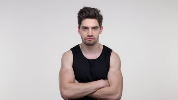 Vážný mladý vousatý sportovník v černé košili se při pohledu na kameru přes šedé pozadí izolovaně rozhněvaný rukou