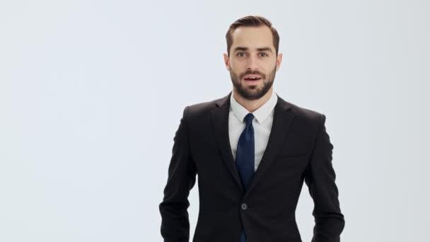 Veselý mladý obchodník v černém obleku a modrý kravata radovat se a dělat gesto vítězů při pohledu na kameru přes šedé pozadí izolované