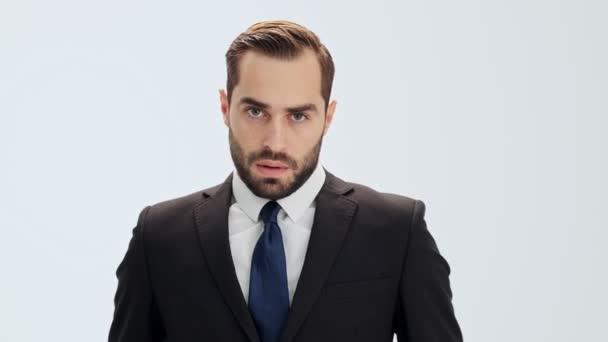 Komoly fiatal üzletember, fekete öltönyt és a kék nyakkendő sóbeles mélyen és készül valami közben figyelmesen néz a kamera felett szürke háttér izolált