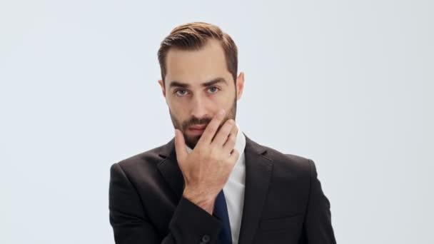 Koncentrált fiatal üzletember, fekete öltönyt és kék nyakkendő gondolkodni valamiről, és megérintette a szakállát, miközben nézi a kamerát, szürke háttér elszigetelt