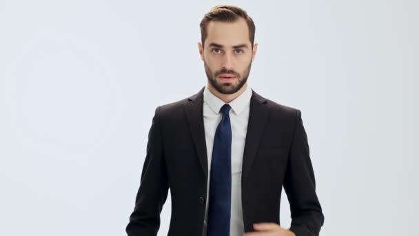 Komoly fiatal üzletember, fekete öltöny és a kék nyakkendő hogy néhány lépést, és gombolta a kabátját, miközben nézi a kamerát szürke háttér elszigetelt