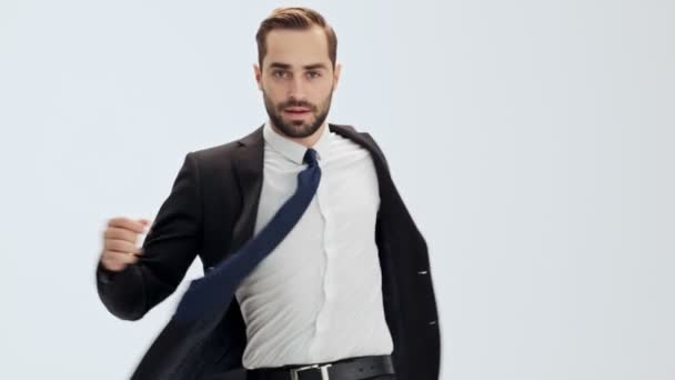 Serious young businessman in black suit and blue tie turning around to the camera and buttoning his jacket over gray background isolated