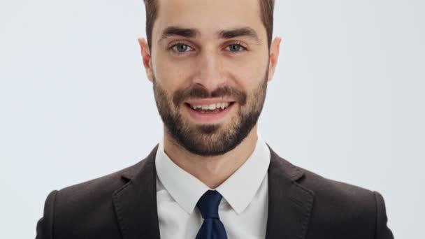 Levágott kilátás vonzó fiatal üzletember, fekete öltöny és a kék nyakkendő mosolyogva, miközben nézi a kamerát, szürke háttér elszigetelt
