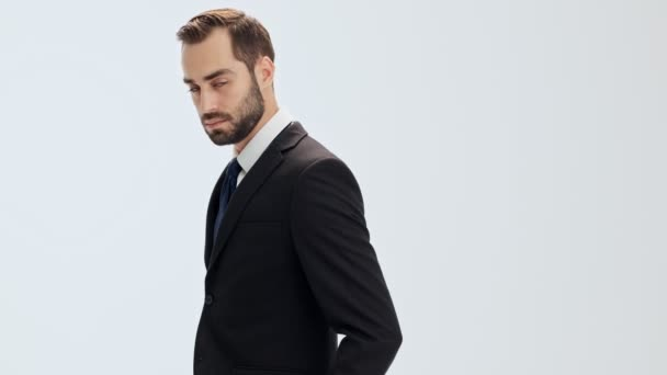 Pensive young businessman in black suit and blue tie raising his head and becoming happy while looking at the camera over gray background isolated