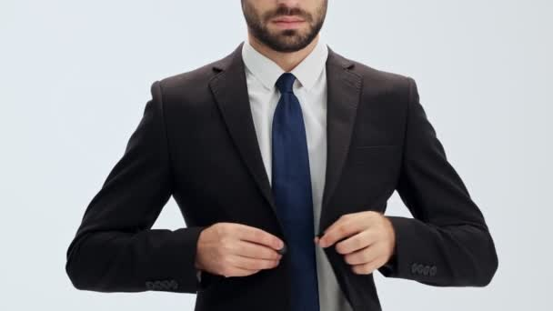 Cropped view of serious young businessman in black suit and blue tie buttoning his jacket and putting his hands in pockets over gray background isolated
