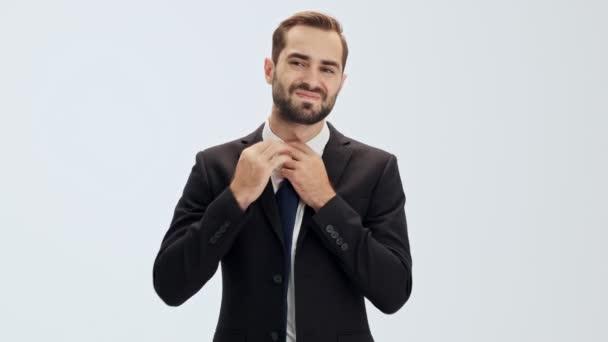 Unavený mladý obchodník v černém obleku s modrou vázankou rozepjal sako a vzal si kravatu, když se díval na kameru přes šedé pozadí izolované