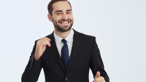 Közelről kilátás vidám fiatal üzletember, fekete öltöny és kék nyakkendő tánc közben nézi a kamerát szürke háttér elszigetelt