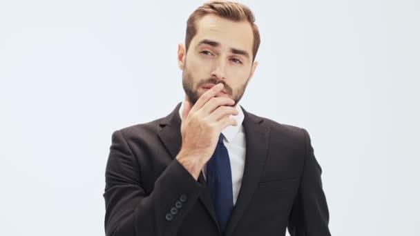 Pensive fiatal üzletember, fekete öltönyt és a kék nyakkendő gondolkodás valamit, és megérintette az állát, miközben nézi a kamerát, szürke háttér elszigetelt