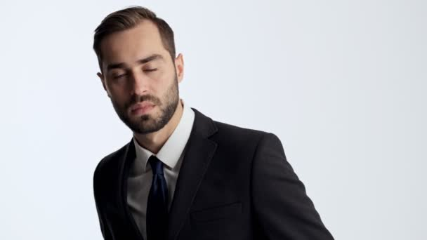 Attractive young businessman in black suit and blue tie feeling angry and rage while looking strict at the camera over gray background isolated