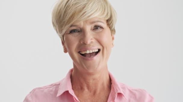 Zblízka pohled na veselou blonďatou ženu, usmívající se a smějící se při pohledu na kameru přes šedé pozadí izolované