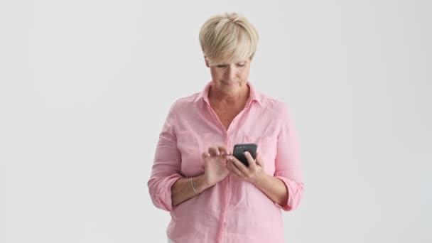 Koncentrovaná Blondýnka, písařské zařízení Smartphone přes šedé pozadí izolované