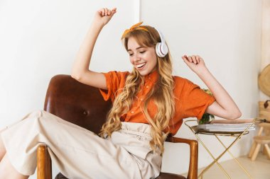 Optimistic smiling young blonde girl at home indoors listening music with headphonws sitting on chair.