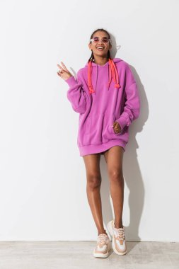 Positive optimistic happy young african stylish woman in pink sweatshirt and sunglasses posing isolated over white wall background showing peace gesture.