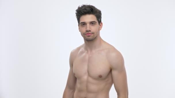 Boční pohled na sebevědomého mladého bruneta s obnažené trupu ukazující jeho biceps s zvedanou paží při pohledu na kameru přes bílé pozadí izolované