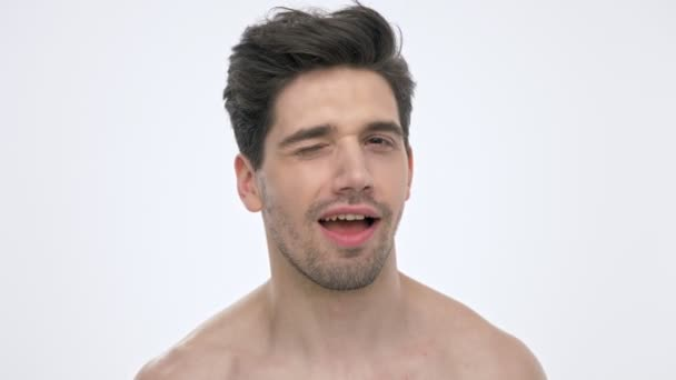 Close up view of cheerful young brunette man with naked torso smiling and winking while looking at the camera over white background isolated