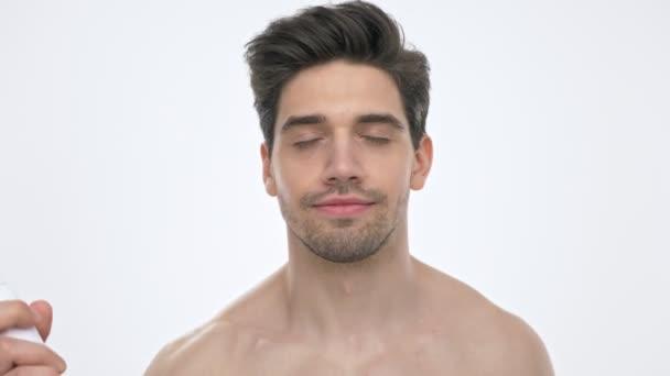 Zavřete pohled na šťastného mladého bruneta, který se s obnažené trupu usmívá a při pohledu na kameru přes bílou pozadí izoloval
