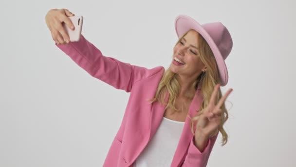 Veselá Mladá blondýnka v růžovém kabátku a na kloboučku při tom, jak se chová na smartphone přes šedé pozadí izolované