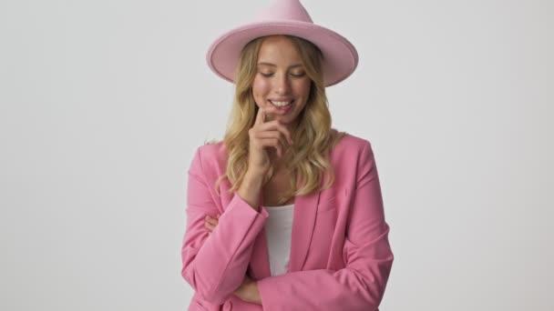 Vidám fiatal szőke nő rózsaszín kabát és a kalap érzés zavart, és becsukta a mosolya kézzel, miközben nézi a kamerát, szürke háttér elszigetelt