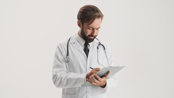 Rozčilený mladý vousatý doktor v bílém profesním kabátě se stetoskem, který se dívá na historii medicíny a vrtěl hlavou záporně přes šedé pozadí izolované