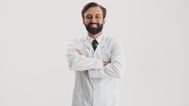 fröhlicher junger bärtiger Mann Arzt in weißem Mantel verschränkte die Arme und lächelte in die Kamera vor grauem Hintergrund isoliert