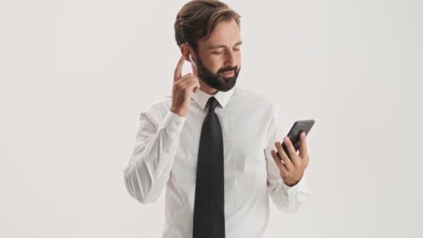 Atraktivní mladý vousatý obchodní muž s bezdrátovými sluchátky s úsměvem a hovopoje, zatímco má hovor na smartphone přes šedé pozadí izolované