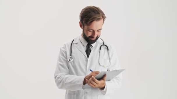 Atraktivní mladý vousatý doktor v bílém profesním kabátě se stetoskem, který pracuje s historií medicíny a pozdraví někoho přes šedé pozadí izolované