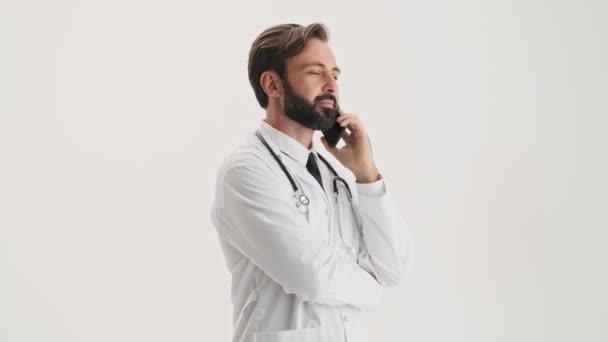 Uklidněte se mladý vousatý doktor v bílém profesním kabátě se stetoskem, který mluví na smartphone přes šedé pozadí izolované