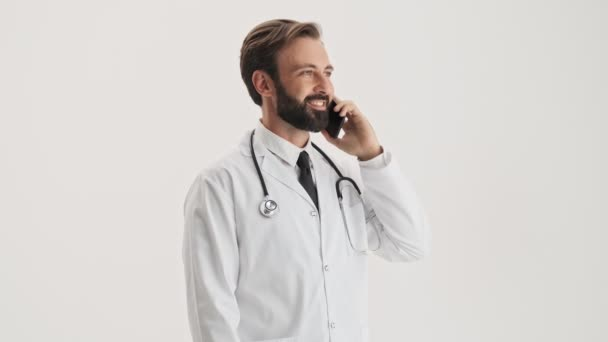 Smiling young bearded man doctor in white professional coat with stethoscope talking on smartphone over gray background isolated