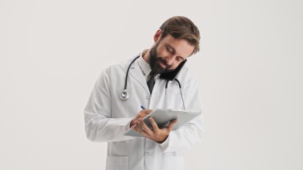 Nespokojen mladý vousatý muž lékař v bílém profesionálním kabátu se stetoskopem pracuje s anamnézou a mluví na smartphone přes šedé pozadí izolované