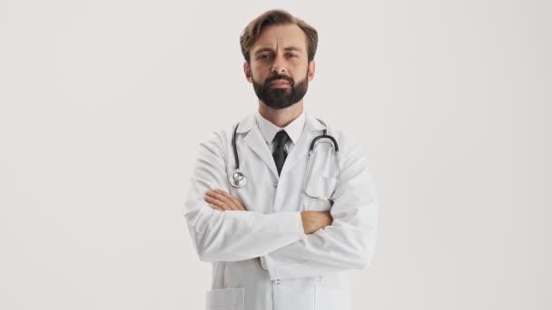 attraktive junge bärtige Mann Arzt in weißem Mantel mit Stethoskop hört jemand aufmerksam zu und schüttelt seinen Kopf positiv, während er in die Kamera über grauem Hintergrund isoliert