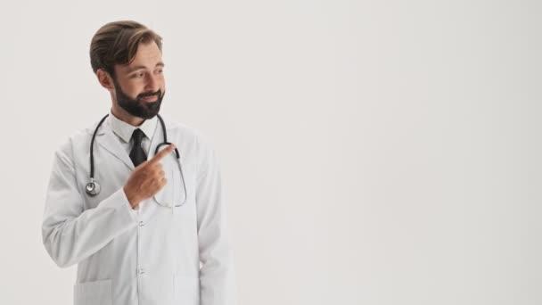 Usmívající se mladý vousatý doktor v bílém profesním kabátě se stetoskem, ukazujícími prstem na stranu a při pohledu na kameru přes šedé pozadí izolované