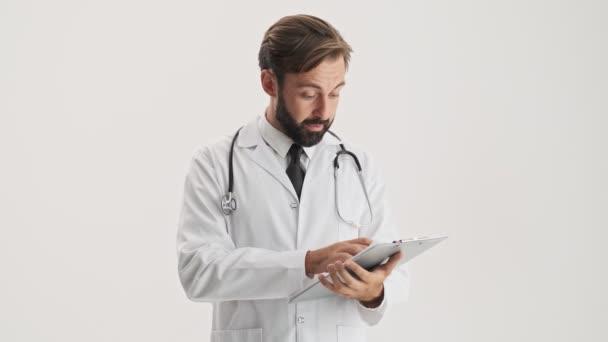 Vážný mladý vousatý doktor v bílém profesním kabátě se stetoskem, který se dívá na lékařskou historii a vrtěl hlavou záporně přes šedé pozadí izolované