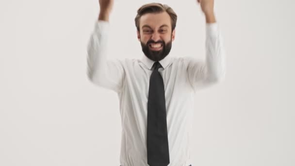Cheerful young bearded business man becoming very excited and making winner gesture with hands while looking at the camera over gray background isolated
