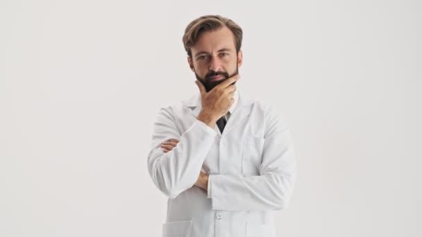 Nachdenkliche junge bärtige Mann Arzt in weißem Mantel berühren seinen Bart und schüttelt seinen Kopf negativ, während Blick in die Kamera über grauen Hintergrund isoliert
