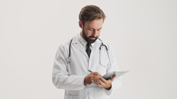 Concentrated young bearded man doctor in white professional coat with stethoscope working with documents attentively over gray background isolated