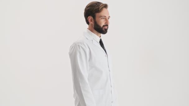Seitenansicht eines lächelnden jungen bärtigen Mannes Arzt in weißem Mantel verschränkte seine Arme und zwinkerte, während er vor grauem Hintergrund isoliert in die Kamera blickte