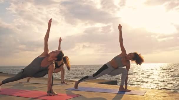 Gruppe konzentrierter junger sportlicher multiethnischer Freundinnen in Sportbekleidung, die Yoga-Übungen auf Matten in Meeresnähe machen