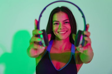 Strong fitness woman isolated with led flash lights give you a headphones.