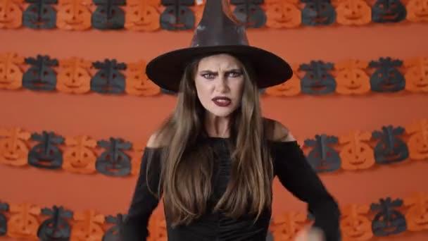 Nespokojeni krásná mladá čarodějnice v černém halloween kostým dostat vztek a brát urážku na někoho přes oranžové dýně zeď