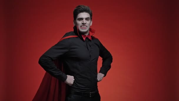 Vampire man with blood and fangs with hands on hips in black halloween costume is roaring isolated over red wall