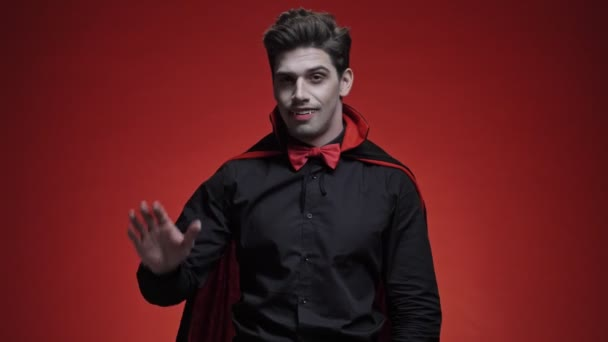 Happy vampire man with blood and fangs in black halloween costume gesturing at camera isolated over red wall