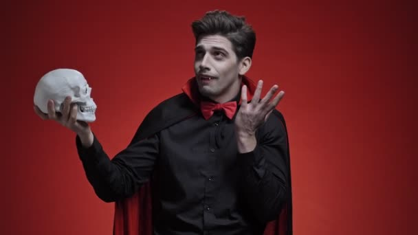 Scary vampire man with fangs in black halloween costume holding human skull in hand and talk to it isolated over red wall